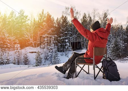Adult Man Blogger Or Freelancer Working On A Laptop In Winter Forest. Freedom, Remote Work Concept.