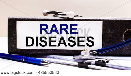 The Desktop Has A Stethoscope, A Blue Pen, And A Gray File Folder With The Text Rare Diseases. Medic