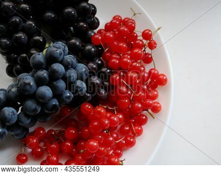 Berry Mix Of Dark Grapes And Viburnum Berries On A White Plate Top View, Bright Garden Fruits To Mai