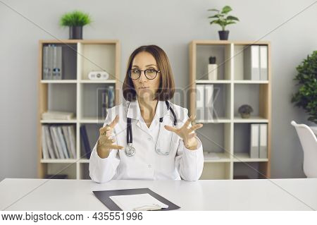 Video Call Portrait Of Professional Physician Sitting At Office Desk And Talking