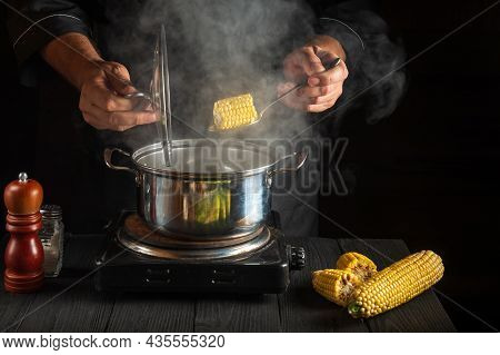 Professional Cook Cooks Corn. Close-up Of A Chef Hands While Cooking In A Restaurant Kitchen. Free A