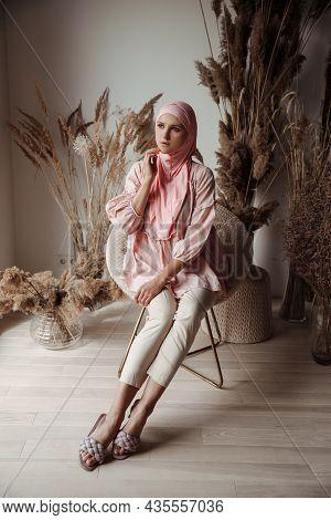 Beautiful Muslim Arabian Woman Wearing Pink Hijab Sitting On Floor And Smiling