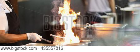 Chef In Rubber Gloves Is Cooking On Fire Closeup