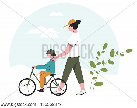 Mom And A Child Are Walking In The Park While Riding A Bicycle. Leisure With Children In The Fresh A