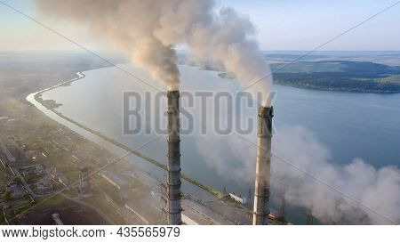 Aerial View Of Coal Power Plant High Pipes With Black Smoke Moving Up Polluting Atmosphere At Sunris
