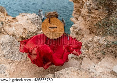 A Girl With Loose Hair In A Long Red Dress Descends The Stairs Between The Yellow Rocks Overlooking