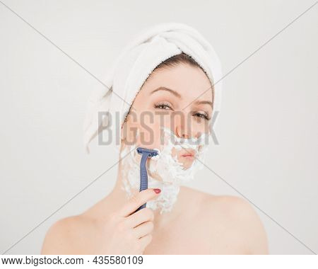 Cheerful Caucasian Woman With A Towel On Her Head And Shaving Foam On Her Face Holds A Razor On A Wh