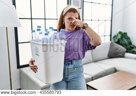 Young redhead woman holding recycling wastebasket with plastic bottles smelling something stinky and disgusting, intolerable smell, holding breath with fingers on nose. bad smell