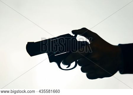 Silhouette Of Hand With Gun On White Background. Man Pulls The Trigger Of Revolver To Fire. Criminal