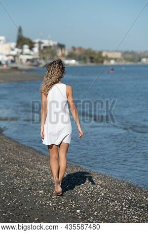 Young Unrecognized Woman Wearing A White Summer Dress Walking In The Beach. Outdoors Lifestyle. Walk