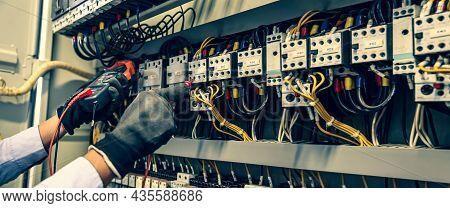 Electricity And Electrical Maintenance Service, Close-up Circuit Breaker Has Engineer Using Measurin