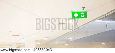 Green Emergency Fire Exit Sign Or Fire Escape On Ceiling For Doorway Or Door Exit  In Building For E
