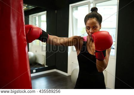 Young Athletic African Woman Boxer With Perfect Physique Punching A Punching Bag At Boxing Gym. Beau