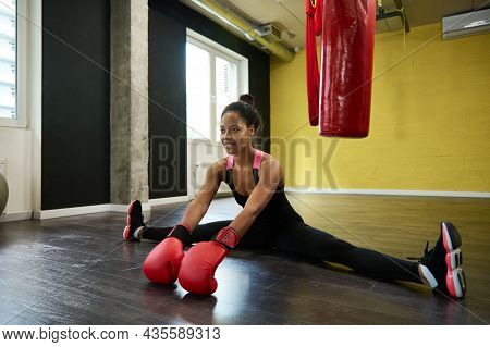 Beautiful Fitness Woman, Female Boxer Wearing Red Boxing Gloves And Sitting On Twine In The Floor Of