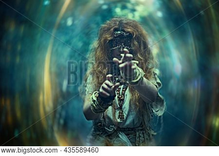 Scary forest witch with a mask covering her eyes in a dark gloomy forest creating a magic portal. Woman shaman. Paganism. Death ritual. Halloween.