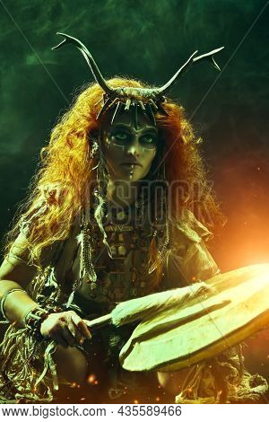 Pagan woman in an ethnic dress and shamanic mascots playing on a shaman frame drum on a dark background with mystical red light. Ethnic traditions. Paganism. Halloween.