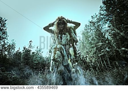 Mysterious shaman woman in a gloomy forest putting on a mask  for doing a magic ritual. Paganism. Death ritual. Halloween.