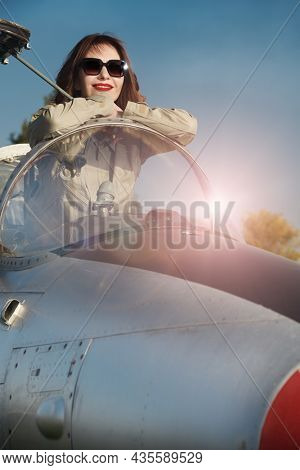 Commercial and military aviation. Beautiful happy woman pilot wearing uniform and sunglasses sits in her aircraft cockpit ready for take off.