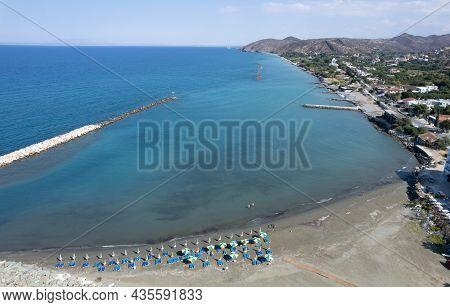 Aerial View, Drone Photograph Of The Coastline Of Pano Pyrgos Village In Cyprus. Beach Umbrellas, Su