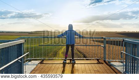 Young Sports Guy Looks At The Agricultural Fields While Standing On The Bridge And Lean On The Raili