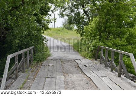 Beautifully Standing Old Wooden Bridge Over River In Colored Background