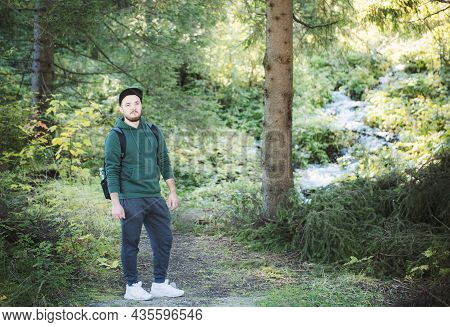 A Man With Backpack Walks In The  Autumn Forest.