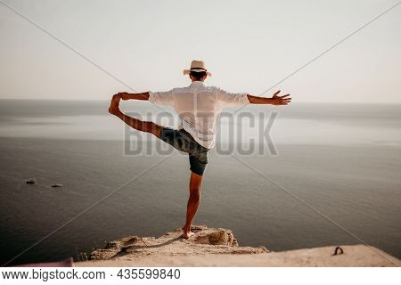A Digital Nomad, A Man In A Hat, A Businessman Does Yoga On The Rocks By The Sea At Sunset Time, Doe