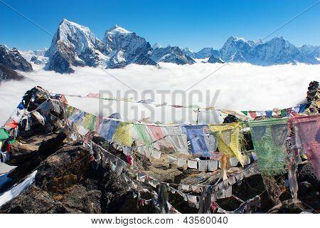 view from Gokyo Ri to Arakam Tse, Cholatse, Tabuche Peak, Thamserku and Kangtega with prayer flags -