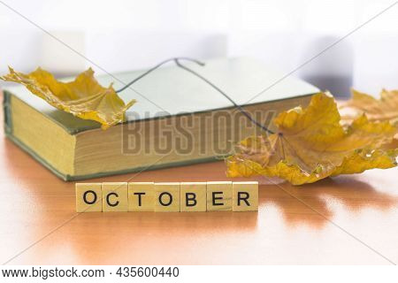 Old Closed Book, Autumn Maple Foliage, Inscription October In Wooden Letters On The Table. Autumn Oc
