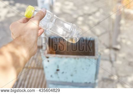 A Man Throws A Plastic Bottle Into A Trash Can.