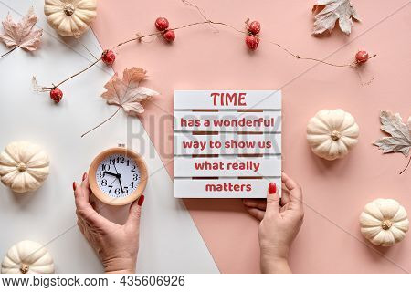 Autumntime Background. Alarm Clock And Pallet With Seasonal Text In Hands. Decorative Pumpkins And N