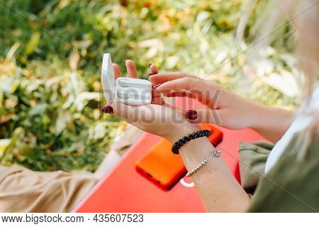 Close-up Of Young Woman And Wireless Earphones Outdoors. Selective Focus On Female Hands Holding Box