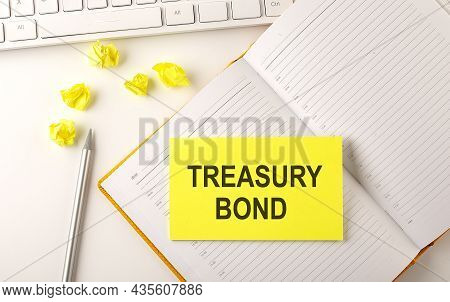 Treasury Bond Text On Sticker On Diary With Keyboard And Pencil
