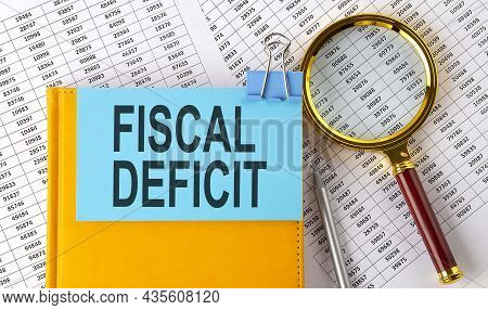 Fiscal Deficit Text On Sticker On Notebook With Magnifier And Chart. Business