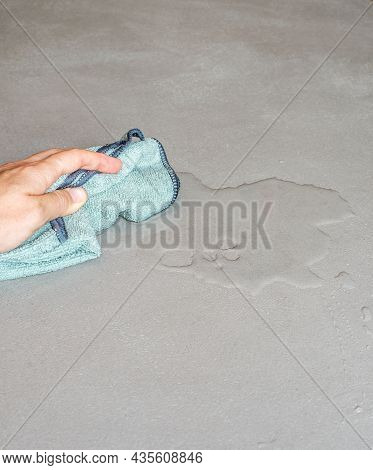 Hand Cleaning Spilled Water On A Cement Floor With A Cloth Dishcloth Drops On A Concrete Floor, Micr