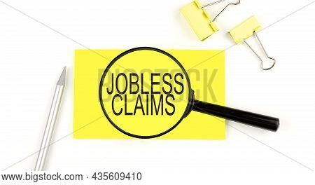 Jobless Claims Text On The Sticker Through Magnifier. View From Above. Business