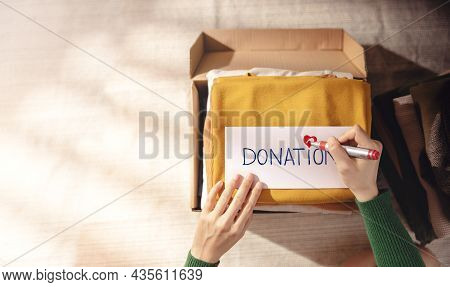 Clothes Donation Concept. Box Of Cloth With Donate Label. Woman Preparing Used Old Garment At Home.