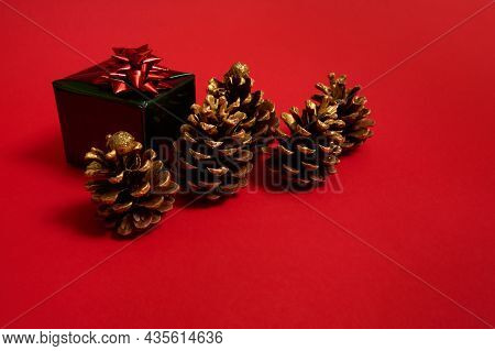 Beautiful Pine Cones Ornate With Golden Paints And Luxury Christmas Gift In Shiny Green Wrapping Pap