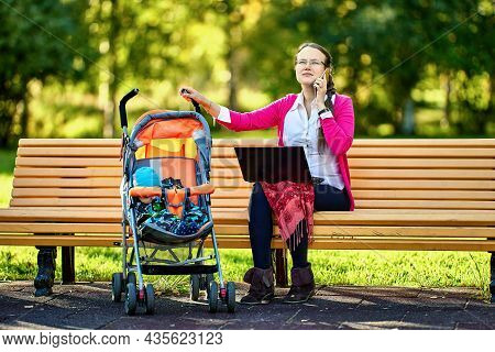 Teleworking By Woman With Infant In Baby Carriage With Help Of Laptop Outdoors.