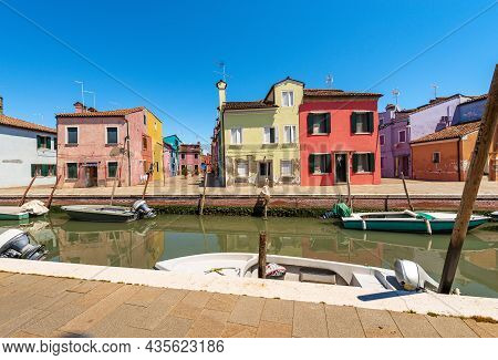 Burano Island With Multi Colored Houses (bright Colors) In Front Of A Small Canal With Small Moored