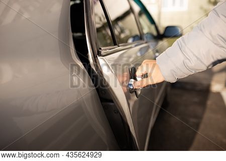 The Man Opens The Back Door Of A Gray Car. The Man Opens The Car Door. Selectiv Focus