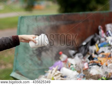 Woman Throwing A Cardboard Glass Into A Recycling Bin. Taking Care Of The Cleanliness Of The City An