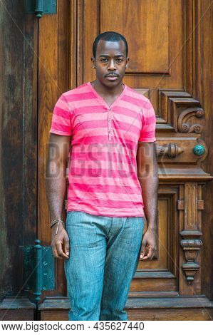 Dressing In A Red, Pink Lines T Shirt And Gray Pants, Wearing A Bracelet, A Young Handsome Black Guy