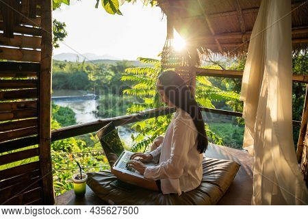 Freelancer Woman Sitting And Writing On The Laptop During Vacation Holidays In Summer Among The Tree