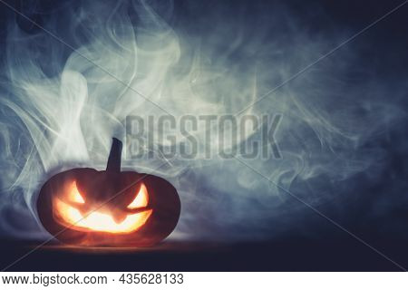Spooky Halloween jack o lantern pumpkin with carved scary grinning face glowing in smoke on Halloween night.