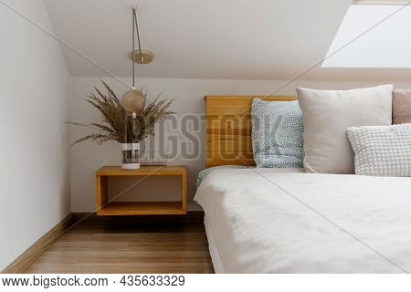 Modern Apartment With Vase On Wood Nightstand Near Comfortable Bed In Cozy Bedroom. Home Decor And W