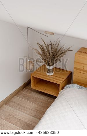 Vertical And High Angle View Of Wooden Nightstand With Home Decor Near Comfortable Bed In Light Bedr