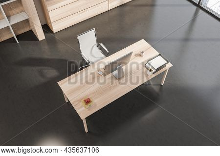 Top View Of Simple Office Interior With Light Wood Office Desk, Mesh Rolling Chair And Dark Grey Con