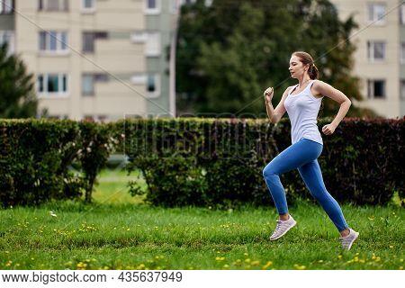 Graceful Woman 29 Years Old In Sportswear Runs Outdoors.