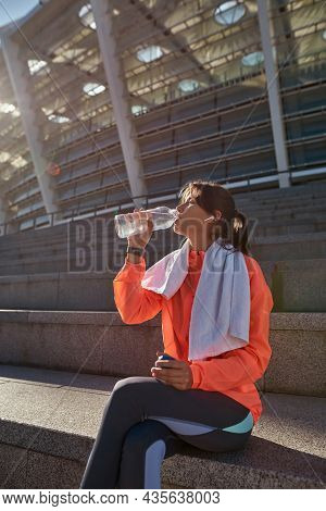 Vertical Narrow Shot Of Thirsty Young Sportswoman Drink Water From Bottle After Workout Training Out